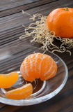 Scheiben der Orange und der reifen Tangerine in der Glasuntertasse Gegen den Hintergrund der alte Holztisch Stockfotografie
