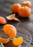 Scheiben der Orange und der reifen Tangerine in der Glasuntertasse Gegen den Hintergrund der alte Holztisch Lizenzfreies Stockbild