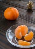 Scheiben der Orange und der reifen Tangerine in der Glasuntertasse Gegen den Hintergrund der alte Holztisch Lizenzfreie Stockfotografie