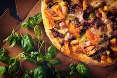 Scheiben der Pizza auf Pappe mit Basilikum Beschneidungspfad eingeschlossen Nahaufnahme Lizenzfreie Stockfotos