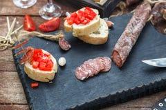 Scheiben der Salami, des Stangenbrots und der Tomate auf dem hölzernen Brett Lizenzfreies Stockfoto