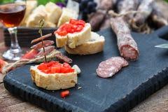 Scheiben der Salami, des Stangenbrots und der Tomate auf dem hölzernen Brett Lizenzfreie Stockfotografie