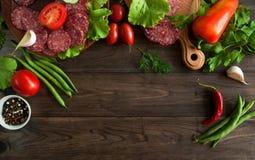 Scheiben der Salami mit Gemüse auf hölzernem Hintergrund Stockfoto