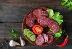Scheiben der Salami mit Gemüse auf hölzernem Hintergrund Lizenzfreies Stockfoto