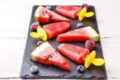 Scheiben der Wassermelone, Fruchteis, gefrorene Blaubeeren, Himbeeren auf schwarzem Brett Lizenzfreies Stockfoto