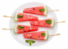 Scheiben der Wassermelone mit Stock auf weißer Platte auf Weiß Stockfoto