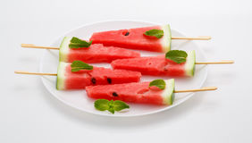 Scheiben der Wassermelone mit Stock auf weißer Platte Es sieht wie IC aus Stockbild