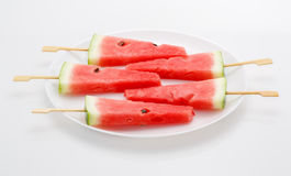 Scheiben der Wassermelone mit Stock auf weißer Platte Es sieht wie IC aus Stockfotografie