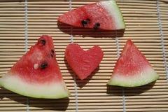 Scheiben der Wassermelone und des Messers auf einer Platte auf einem hölzernen Hintergrund Lizenzfreie Stockfotografie