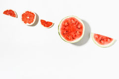 Scheiben der Wassermelone und der Pampelmuse auf weißem Hintergrund flaches La Stockbilder