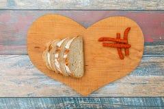 Scheiben des frischen Brotes und der trockenen Rauchwurst auf Holztisch stockbilder