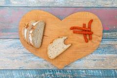Scheiben des frischen Brotes und der trockenen Rauchwurst auf Holztisch lizenzfreies stockfoto