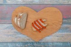 Scheiben des frischen Brotes und der trockenen Rauchwurst auf Holztisch lizenzfreie stockfotografie