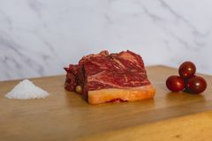 Scheiben des frischen rohen Rindfleischsteaks auf hölzernem Brett auf weißem Hintergrund mit vielen von Pyramide des groben Salze lizenzfreies stockbild