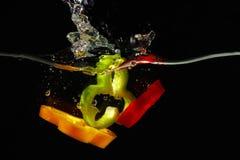 Scheiben des frischen roten, grünen, gelben Pfeffers im Wasser Stockbild