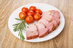 Scheiben des gebackenen carbonade, Tomaten Kirsche, Rosmarin in der Platte Lizenzfreie Stockfotos