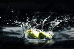 Scheiben des Kalkes fallend in Wasser Lizenzfreie Stockfotos