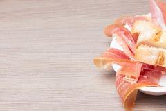 Scheiben des kurierten Schweinefleischschinkens mit Brot Lizenzfreie Stockfotos