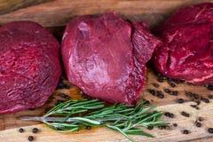 Scheiben des Rindfleischsteaks auf einer hölzernen Platte Lizenzfreie Stockbilder