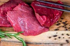 Scheiben des Rindfleischsteaks auf einer hölzernen Platte Stockfotos