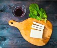 Scheiben des rohen Tofus, des Spinats und des Weins Lizenzfreies Stockfoto