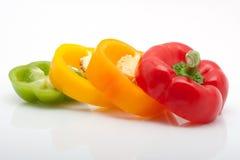 Scheiben des roten, grünen, gelben und orange Pfeffers getrennt auf weißem Hintergrund Stockfoto