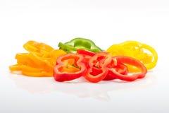 Scheiben des roten, grünen, gelben und orange Pfeffers getrennt auf weißem Hintergrund Lizenzfreie Stockfotos