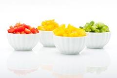 Scheiben des roten, grünen, gelben und orange Pfeffers getrennt auf weißem Hintergrund Lizenzfreies Stockfoto