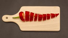 Scheiben des roten Pfeffers, geschnittenes Stück Pfeffer auf hölzernem Schneidebrett Stockbild