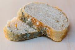 Scheiben des schimmeligen Brotes auf hellem Hintergrund Nahrung nicht passend für Verbrauch lizenzfreie stockfotografie