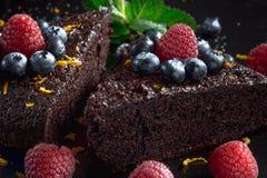 Scheiben des selbst gemachten Schokoladenkuchens verziert mit Himbeeren und Blaubeeren Lizenzfreie Stockbilder