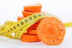 Scheiben einer Karotte mit einem Maß nehmen eingewickelt herum lokalisiert auf einem weißen Hintergrund auf Stockfotografie