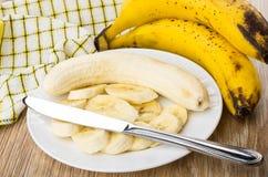 Scheiben von Bananen in der Platte und im Messer auf Tabelle Stockbild
