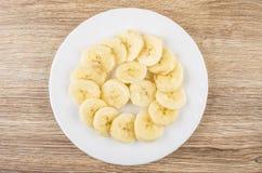 Scheiben von Bananen in der weißen Platte auf Holztisch Stockfotografie