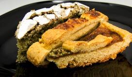 Scheiben von drei unterschiedlichen selbst gemachten Törtchen und von Torte auf einem schwarzen Teller Für Nahrungsmittelkonzepte Stockbilder