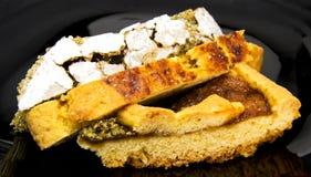 Scheiben von drei unterschiedlichen selbst gemachten Törtchen und von Torte auf einem schwarzen Teller Für Nahrungsmittelkonzepte Lizenzfreie Stockfotos