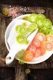 Scheiben von grünen und rosa Tomaten auf einer weißen Platte Stockfotos