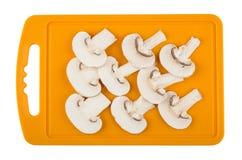 Scheiben von Pilzen auf dem orange Schneidebrett lokalisiert auf Weiß Stockfotos
