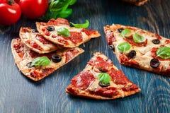 Scheiben von Pizzapepperonis mit Oliven Stockfoto