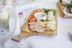 Scheiben von verschiedenen gesalzenen Fischen - Lachse, muksun, öliger Fisch auf hölzernem Schneidebrett Restaurant stockfotos