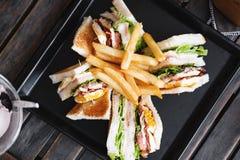 Scheibensandwiche mit Franzosen brieten, auf schwarzem Teller, auf Holztisch, Draufsicht Lizenzfreies Stockfoto