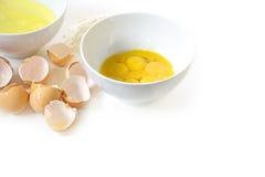 Scheid de eieren voor baksel, eierdooier en eiwit in kommen Stock Foto's
