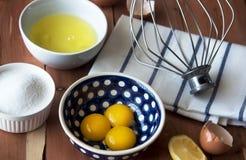 Scheiding de dooier van ei in weinig kom en en voorbereiding voor het zwaaien van eiwit en dooiers stock foto's