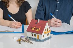 Scheiding en het verdelen van een bezitsconcept De man en de vrouw ondertekenen scheidingsovereenkomst stock foto's