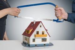 Scheiding en het verdelen van een huisconcept De man en de vrouw verdelen model van huis met zaag Royalty-vrije Stock Afbeelding
