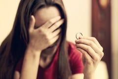 Scheidingsconcept Droevige eenzame de verlovingsringzitting van de vrouwenholding bij binnenlands huisclose-up Selectieve nadruk stock afbeelding