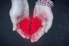 Scheidingsconcept - Explosie van Gebroken hart in de mannelijke handen zwart-wit foto met rood hart blak en wit stock fotografie