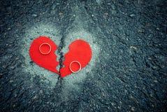 Scheidingsconcept - gebroken hart met trouwringen op gebarsten asfalt gestemd stock foto
