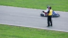Scheidsrechter die zich op een het rennen spoor met raceauto's bevinden die overgaan door stock video