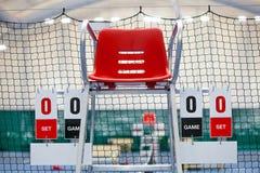 Scheidsrechterstoel met scorebord op een tennisbaan vóór het spel stock afbeelding